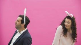 Situación joven hermosa de los pares en fondo rosado Al mismo tiempo, la muchacha aplaude a su marido, él a su vez la muerde