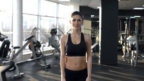 Situación juguetona hermosa de la mujer en gimnasio y sonrisa, forma de vida activa, entrenamiento fotos de archivo libres de regalías