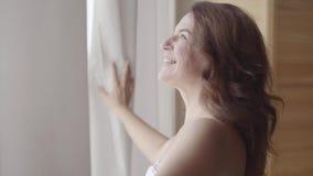 Situación madura bonita del cordón de la cortina de abertura de la mujer en el apartamento de lujo casero o el hotel moderno que  almacen de metraje de vídeo