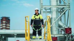Situación masculina confiada del trabajador del metal en torre y mirada en territorio de la fábrica grande almacen de video
