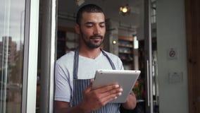Situaci?n masculina del due?o en la entrada del caf? usando la tableta digital metrajes
