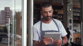 Situaci?n masculina del due?o en la entrada de su caf? que sostiene la tableta digital metrajes