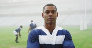 Situación masculina del jugador del rugbi con los brazos cruzados en el estadio 4k almacen de video