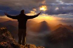 Situación masculina joven del caminante en el pico de la montaña fotografía de archivo libre de regalías