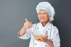 Situación mayor del estudio del cocinero de la mujer aislada en los huevos que baten grises para el desayuno que mira el primer f imagen de archivo