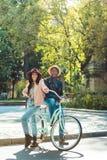 Situación multicultural hermosa de los pares así como una bicicleta y presentación a imágenes de archivo libres de regalías