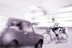 Situación peligrosa del tráfico de ciudad con un ciclista y un coche Foto de archivo libre de regalías