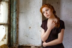 Situación pelirroja triste de la muchacha cerca de una ventana quebrada, del concepto de pobreza y de la miseria imágenes de archivo libres de regalías