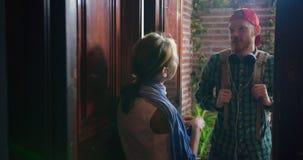 Situación que habla del individuo y de la muchacha en el vestíbulo en la puerta abierta, primer metrajes