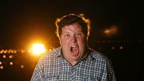 Situación rabiada gorda del hombre y griterío en pánico o terror en la noche al aire libre, retrato metrajes