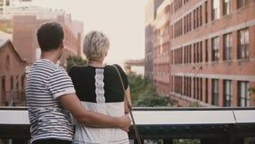 Situación romántica feliz de los pares cercana y que abraza, hablando y gozando sorprendiendo la opinión de puente de Brooklyn en almacen de metraje de vídeo