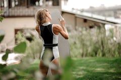 Situación rubia delgada de la muchacha de la vista posterior con el wakeboard imagenes de archivo