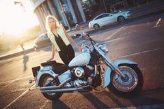 Situación rubia hermosa de la mujer joven cerca de una motocicleta en el b Imagen de archivo