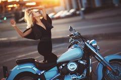 Situación rubia hermosa de la mujer joven cerca de una motocicleta en el b Imágenes de archivo libres de regalías