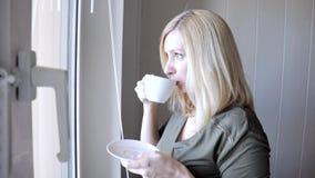 Situación rubia hermosa thinkful triste joven de la mujer cerca de la ventana con las persianas por la mañana y el café de consum almacen de video
