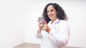 Situación sonriente del doctor de sexo femenino latino de sexo femenino que mira su teléfono en su oficina con el estetoscopio en fotografía de archivo