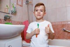Situación sonriente del muchacho en el cuarto de baño con su cepillo de dientes y su pulgar para arriba Concepto dental de la hig imagen de archivo libre de regalías