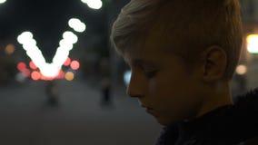 Situación triste del muchacho sola en la calle en la falta del problema de la víspera del día de fiesta que tiraniza de amigos almacen de video