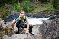 Situación turística del muchacho cerca de la cascada de la montaña Imagen de archivo libre de regalías