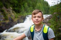 Situación turística del muchacho cerca de la cascada de la montaña Fotografía de archivo