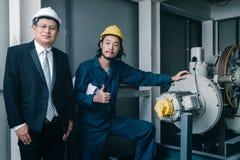 Situación y sonrisa asiáticas de los ingenieros a la cámara fotografía de archivo libre de regalías