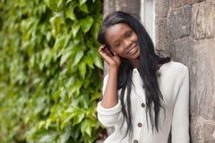 Situación y sonrisa jovenes de la mujer del afroamericano foto de archivo