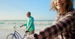 Situaci?n cauc?sica mayor activa de los pares con la bicicleta en la playa 4k almacen de metraje de vídeo