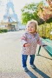 Situaci?n de un a?o de la muchacha al lado de un banco en Par?s, con la torre Eiffel detr?s de ella fotografía de archivo