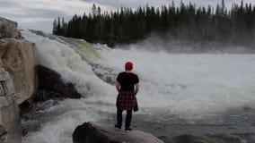 Situaci?n del hombre del viaje delante de la cascada en el bosque de Noruega en la madrugada Vestido en un sombrero rojo metrajes