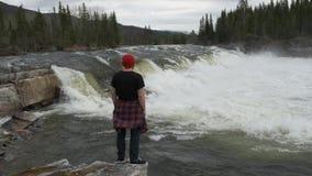 Situaci?n del hombre del viaje delante de la cascada en el bosque de Noruega en la madrugada Vestido en un sombrero rojo almacen de metraje de vídeo