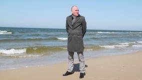 Situaci?n elegante vestida del hombre en la playa del mar y con confianza de la mirada sobre el horizonte Concepto del asunto almacen de metraje de vídeo