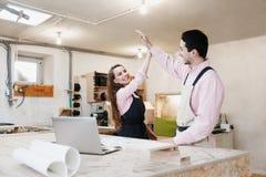 Situaci?n feliz joven de la familia en un banco de trabajo en un taller de la carpinter?a, escribiendo un proyecto Negocio famili imagen de archivo libre de regalías
