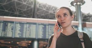 Situaci?n hermosa joven de la mujer en el aeropuerto que invita al tel?fono metrajes