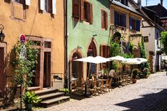 RIQUEWIHR, FRANCE - JULY 17, 2017: Picturesque street with traditional colorful houses in Riquewihr village on alsatian wine route Royalty Free Stock Image