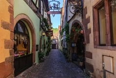 RIQUEWIHR, FRANCE - JULY 17, 2017: Picturesque street with traditional colorful houses in Riquewihr village on alsatian wine route Royalty Free Stock Images