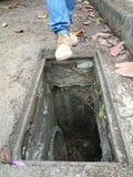 Situation dangereuse quand d'homme une chute presque dans un drain Photos libres de droits