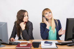 The situation in the office - a girl with a puzzled look on his colleague is talking on the phone. Two young beautiful girls colleagues sitting at the same desk royalty free stock photos