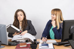 The situation in the office - one employee overburdened, the other does nothing and laughs looking at her Stock Photos