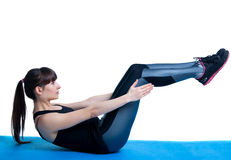 Situps. Beautiful sporty brunette woman model wearing sportswear tights and top, lying on a blue mat, doing crunches and situps, knees bent. Isolated on white Royalty Free Stock Photo