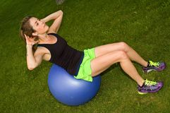 Situps on exercise ball. Young woman doing situps in a park on an exercise ball Stock Photo