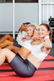 Situps in gym. Group of people doing situps in gym Stock Images