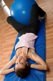 Situps with a Pilates Ball. A woman doing sit ups on an exercise mat with a blue pilates ball Royalty Free Stock Photo