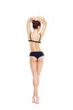 Sitz-, gesunde und sportlichefrau im schwarzen Badeanzug lokalisiert auf Weiß Stockfotos