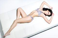 Sitz-, sportliche und sexyjunge Frau in einem Badeanzug Stockfoto