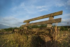 Bench in clear natural under blue sky with small veil clouds Royalty Free Stock Photography