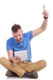 Sitzbeifall des jungen Mannes mit Laptop in der Hand Stockbilder