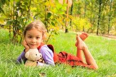 Sitze des kleinen Mädchens auf der Wiese Stockfotografie