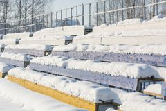 Sitze im Stadion unter dem Schnee Stühle für Zuschauer am Stadion unter dem Schnee lizenzfreies stockfoto