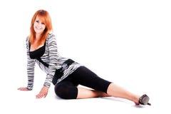 Sitzen auf dem lächelnden reizenden jungen Mädchen des Fußbodens lizenzfreies stockfoto