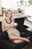Sitzen auf dem Sofa, das von einem Cup trinkt Stockfotos